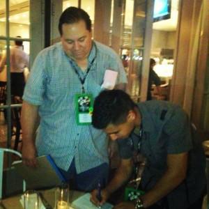 Manager Cameron  watches Alexis Zazueta sign contract